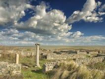 Δραματικός μπλε ουρανός με τα άσπρα σύννεφα πέρα από τις καταστροφές μιας στήλης αρχαίου Έλληνα σε Histria, στις ακτές Μαύρης Θάλ Στοκ Εικόνες