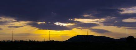 Δραματικός ουρανός ηλιοβασιλέματος των δονούμενων πορτοκαλιών, κίτρινων και πορφυρών χρωμάτων ουρανού με τις σκιαγραφίες των φανα στοκ φωτογραφίες