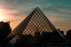 Δραματικός ουρανός σκιαγραφιών πυραμίδων του Λούβρου στοκ εικόνες