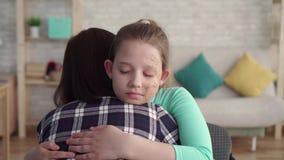 Δραματικός πυροβολισμός ενός κοριτσιού με μια του προσώπου ατέλεια που αγκαλιάζει τη μητέρα της απόθεμα βίντεο