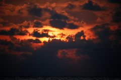 Δραματικό ηλιοβασίλεμα με τα σύννεφα στο πορτοκαλί φως του ήλιου Φλεμένος ηλιοβασίλεμα με το φως που περνά μέσω των σκοτεινών σύν Στοκ Εικόνα