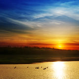 Δραματικό ηλιοβασίλεμα πέρα από τον ποταμό Στοκ Φωτογραφία