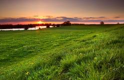 Δραματικό ηλιοβασίλεμα πέρα από το ανθίζοντας λιβάδι Στοκ Εικόνα