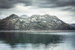 Δραματικό τοπίο με τα βουνά στην ακτή και ήρεμο νερό με την αντανάκλαση ουρανού στη συννεφιάζω ημέρα με το δραματικό ουρανό στην  Στοκ Εικόνα