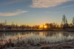 Δραματικό χειμερινό τοπίο με την παγωμένη λίμνη και την ανατολή Στοκ Φωτογραφίες