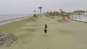 Δραστήριο αθλητικό θηλυκό που τρέχει στην παραλία μεταξύ του αχύρου parasols, εναέρια άποψη φιλμ μικρού μήκους