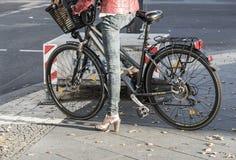 Δραστήριο θηλυκό με το ποδήλατο που στέκεται στην οδό Στοκ φωτογραφία με δικαίωμα ελεύθερης χρήσης