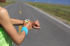 Δρομέας γυναικών έτοιμος να τρέξει το σύνολο και την εξέταση το αθλητικό έξυπνο ρολόι Στοκ Φωτογραφίες