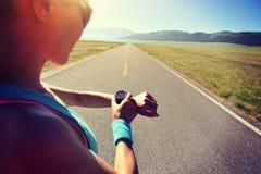 Δρομέας γυναικών έτοιμος να τρέξει το σύνολο και την εξέταση το αθλητικό έξυπνο ρολόι Στοκ Εικόνες