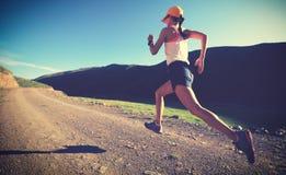 Δρομέας γυναικών που τρέχει στο ίχνος βουνών στοκ εικόνες