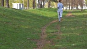 Δρομέας γυναικών που τρέχει στο πάρκο σε σε αργή κίνηση Όμορφο φίλαθλο πρότυπο ικανότητας κατά τη διάρκεια του υπαίθριου workout απόθεμα βίντεο