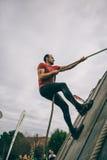 Δρομέας που αναρριχείται στον τοίχο με ένα σχοινί στη δοκιμή της ακραίας φυλής εμποδίων Στοκ εικόνες με δικαίωμα ελεύθερης χρήσης