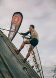 Δρομέας που αναρριχείται στον τοίχο με ένα σχοινί στη δοκιμή της ακραίας φυλής εμποδίων Στοκ Φωτογραφίες