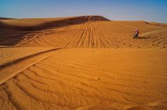Δρομέας στη μοτοσικλέτα στους αμμόλοφους άμμου ερήμων του Ντουμπάι στοκ εικόνες