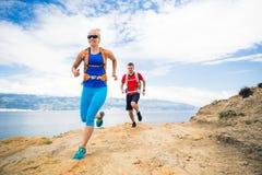 Δρομείς ζεύγους που τρέχουν με τα σακίδια πλάτης στο ίχνος rocku στην παραλία Στοκ Φωτογραφία