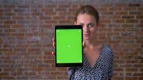 Δροσίστε την καυκάσια ταμπλέτα εκμετάλλευσης brunette θηλυκή με την πράσινη οθόνη στεμένος ακόμα στο κόκκινο στούντιο τούβλου απόθεμα βίντεο