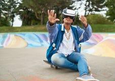 Δροσίστε τη χιλιετή μαύρη γυναίκα με τα γυαλιά εικονικής πραγματικότητας, skateboard σε ένα υπαίθριο πάρκο σαλαχιών Στοκ εικόνα με δικαίωμα ελεύθερης χρήσης