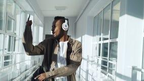 Δροσίστε τον ευτυχή χορό τύπων αφροαμερικάνων ακούοντας τη μουσική στα ακουστικά που περπατούν και που περνούν από την ομάδα συμμ φιλμ μικρού μήκους