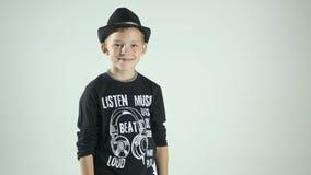 Δροσίστε το αρκετά μοντέρνο μικρό παιδί με το καπέλο που απομονώνεται στο άσπρο υπόβαθρο απόθεμα βίντεο