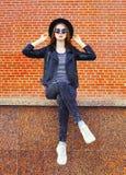 Δροσερή γυναίκα μόδας αρκετά στη μαύρη συνεδρίαση ύφους βράχου στην πόλη πέρα από τα τούβλα Στοκ εικόνα με δικαίωμα ελεύθερης χρήσης