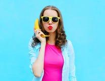 Δροσερή γυναίκα πορτρέτου αρκετά με την μπανάνα που έχει τη διασκέδαση πέρα από ζωηρόχρωμο Στοκ εικόνα με δικαίωμα ελεύθερης χρήσης