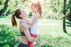 Δροσερή εικόνα της μητέρας και της κόρης που στέκονται έξω στο πάρκο Η γυναίκα κρατά την κόρη της σε ετοιμότητα της και εξετάζει Στοκ εικόνα με δικαίωμα ελεύθερης χρήσης