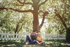 Δροσερή εικόνα της συνεδρίασης πατέρων και γιων μαζί κάτω από το μεγάλο και πράσινο δέντρο Εξετάζουν την οθόνη lap-top ` s Είναι Στοκ φωτογραφία με δικαίωμα ελεύθερης χρήσης