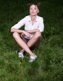 Δροσερή νέα γυναίκα που θέτει τη συνεδρίαση στη χλόη cross-legged στοκ φωτογραφία με δικαίωμα ελεύθερης χρήσης