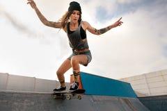 Δροσερή νέα γυναίκα που κάνει σκέιτ μπορντ στο πάρκο σαλαχιών Στοκ Εικόνες