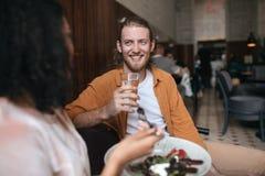 Δροσερή συνεδρίαση ατόμων στο εστιατόριο και ομιλία με το κορίτσι Συνεδρίαση αγοριών χαμόγελου στον καφέ με το ποτήρι του νερού υ Στοκ Φωτογραφίες
