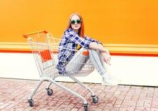 Δροσερή συνεδρίαση κοριτσιών μόδας στο κάρρο καροτσακιών αγορών Στοκ φωτογραφίες με δικαίωμα ελεύθερης χρήσης