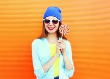 Δροσερή χαμογελώντας γυναίκα πορτρέτου αρκετά και lollipop πέρα από το ζωηρόχρωμο πορτοκάλι Στοκ Εικόνες