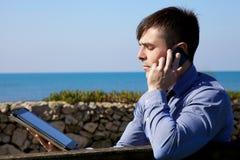 Δροσερός επιχειρηματίας που εργάζεται με την ταμπλέτα και το τηλέφωνο υπαίθρια Στοκ εικόνα με δικαίωμα ελεύθερης χρήσης
