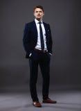 Δροσερός επιχειρηματίας που στέκεται στο γκρι Στοκ φωτογραφία με δικαίωμα ελεύθερης χρήσης
