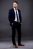 Δροσερός επιχειρηματίας που στέκεται στο γκρι Στοκ Φωτογραφία