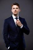 Δροσερός επιχειρηματίας που στέκεται στο γκρι Στοκ Εικόνες