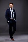 Δροσερός επιχειρηματίας που στέκεται στο γκρι Στοκ Εικόνα