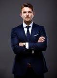 Δροσερός επιχειρηματίας που στέκεται στο γκρι Στοκ εικόνα με δικαίωμα ελεύθερης χρήσης