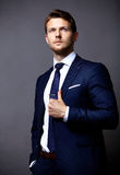 Δροσερός επιχειρηματίας που στέκεται στο γκρι Στοκ Φωτογραφίες