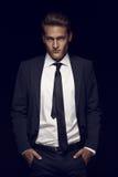 Δροσερός επιχειρηματίας που στέκεται στο σκοτεινό υπόβαθρο Στοκ Εικόνα