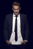Δροσερός επιχειρηματίας που στέκεται στο σκοτεινό υπόβαθρο Στοκ Εικόνες