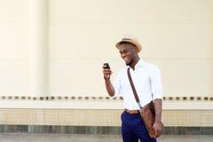 Δροσερός νέος μαύρος που εξετάζει το κινητό τηλέφωνο Στοκ εικόνες με δικαίωμα ελεύθερης χρήσης
