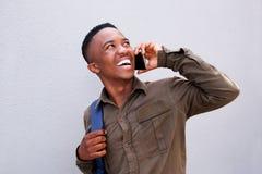 Δροσερός νέος μαύρος τύπος που γελά και που μιλά στο κινητό τηλέφωνο Στοκ εικόνες με δικαίωμα ελεύθερης χρήσης