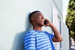 Δροσερός νέος μαύρος τύπος που γελά και που μιλά στο τηλέφωνο κυττάρων Στοκ εικόνα με δικαίωμα ελεύθερης χρήσης