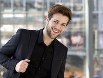 Δροσερός νέος τύπος που χαμογελά με το μαύρο κοστούμι Στοκ Εικόνες