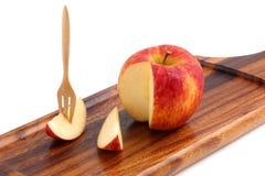 Δροσερός οργανικός φρέσκος κόκκινος ξύλινος δίσκος μήλων με το δίκρανο στο W Στοκ Εικόνα