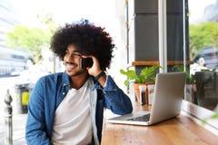 Δροσερός τύπος που χρησιμοποιεί το κινητά τηλέφωνο και το lap-top Στοκ Φωτογραφία