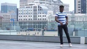 Δροσερός τύπος στην κάσκα που εκτελεί afrohouse το χορό απόθεμα βίντεο
