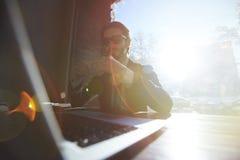 Δροσερός όμορφος επιχειρηματίας με το lap-top στον καφέ Στοκ Φωτογραφίες