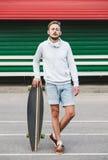 Δροσερό αγόρι που στέκεται με το longboard Στοκ Εικόνες